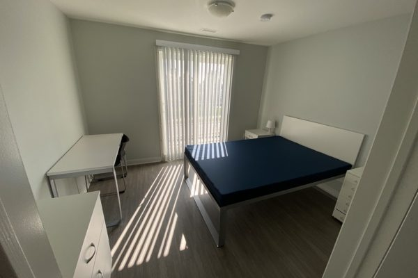 Suite bedroom with bed, desk, dresser and night stands